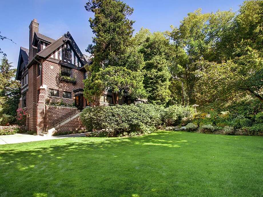 Grounds of the O.W. Fisher House, at 1039 Belmont Place E., which is now for sale. The 8,243-square-foot brick Tudor, built in 1913, has five bedrooms, 6.25 bathrooms, a library, a sun room, five fireplaces, wood walls, beamed ceilings, leaded glass, built-ins, a patio and views of Puget Sound, Lake Union and the Olympic Mountains on a 7,200-square-foot manicured lot. It's listed for $2.9 million. Photo: Courtesy Bob Bennion And Mary Snyder, Windermere Real Estate