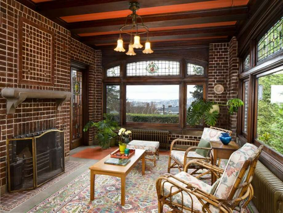 Sun room of the O.W. Fisher House, at 1039 Belmont Place E., which is now for sale. The 8,243-square-foot brick Tudor, built in 1913, has five bedrooms, 6.25 bathrooms, a library, five fireplaces, wood walls, beamed ceilings, leaded glass, built-ins, a patio and views of Puget Sound, Lake Union and the Olympic Mountains on a 7,200-square-foot manicured lot. It's listed for $2.9 million. Photo: Courtesy Bob Bennion And Mary Snyder, Windermere Real Estate