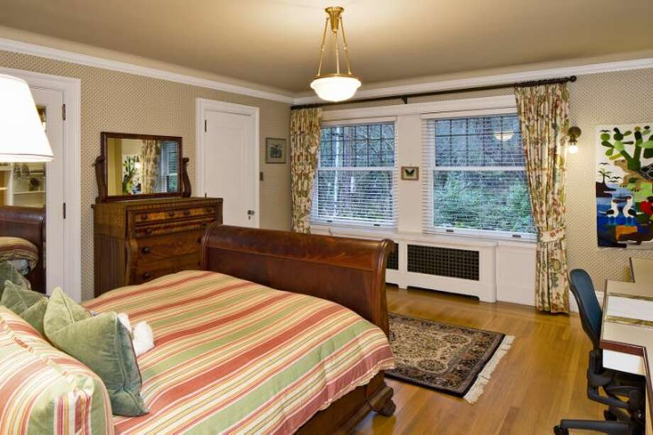 Bedroom of the O.W. Fisher House, at 1039 Belmont Place E., which is now for sale. The 8,243-square-foot brick Tudor, built in 1913, has five bedrooms, 6.25 bathrooms, a library, a sun room, five fireplaces, wood walls, beamed ceilings, leaded glass, built-ins, a patio and views of Puget Sound, Lake Union and the Olympic Mountains on a 7,200-square-foot manicured lot. It's listed for $2.9 million. Photo: Courtesy Bob Bennion And Mary Snyder, Windermere Real Estate