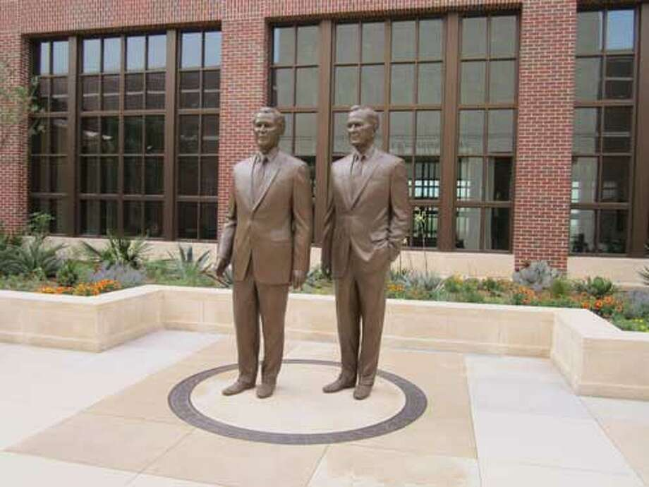 The statues of George W. Bush and his father, George H.W. Bush, are in a patio next to Freedom Hall at Dallas' George W. Bush Presidential Library and Museum. Staff/David Hendricks
