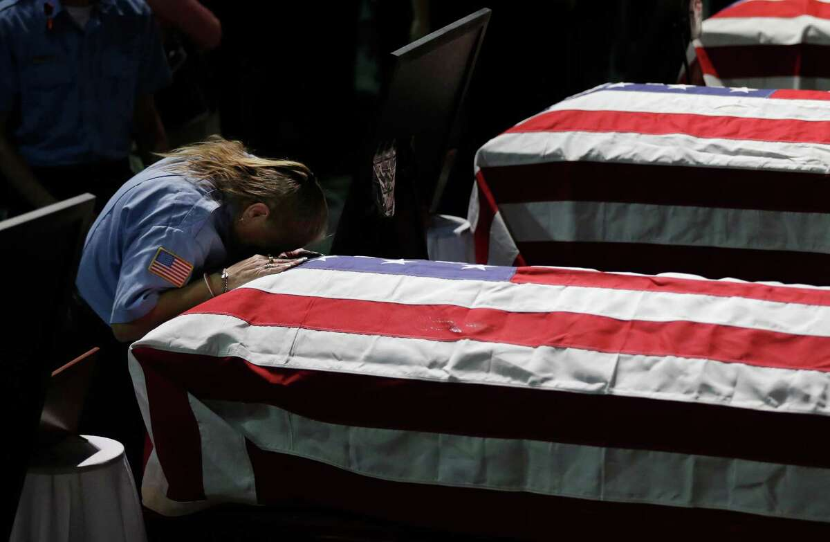 West EMT Terase Alexander leans on the casket of West firefighter Cyrus Reed. (AP Photo/Eric Gay)