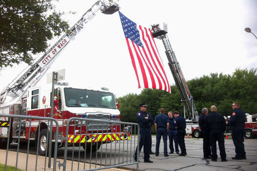 A large flag drapes between ladder trucks from the Waco and Bellmead fire departments outside a massive memorial service for fallen first responders at Baylor University. Photo: Craig Kapitan / Express-News