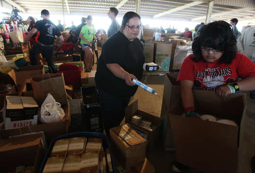 Nicole Lopez and her 15-year-old daughter, Gabby, from West, Texas put supplies in a box for Lopez's aunt at a distribution center to help those affected from the West Fertilizer explosion on Friday, Apr. 19, 2013. Lopez said her home was not affected from the blast. Photo: Kin Man Hui, San Antonio Express-News / ©2013 San Antonio Express-News