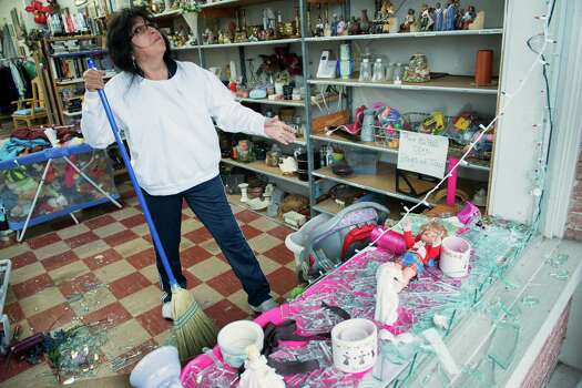 Maria Galvan cleans up broken glass from the blown out front windows of the West Thrift Shop. Photo: Smiley N. Pool, Houston Chronicle / © 2013  Houston Chronicle