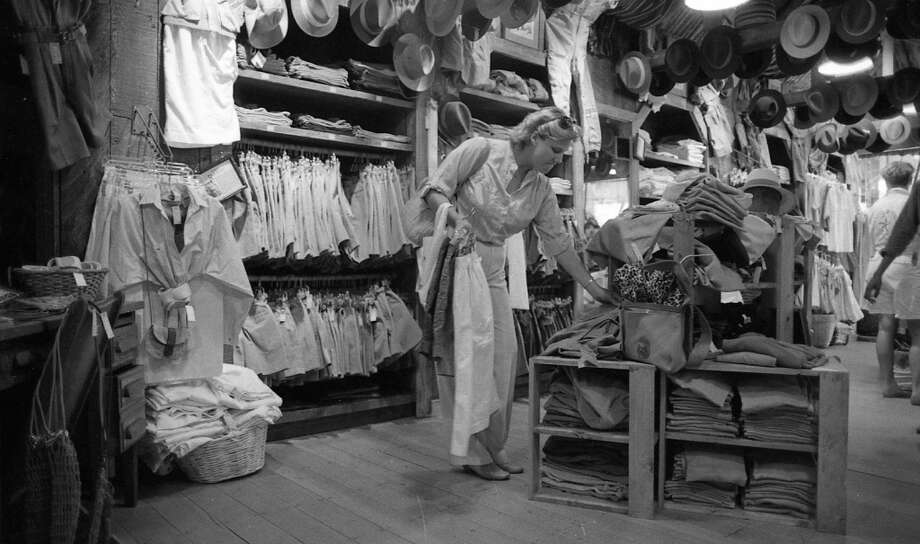 "July 9. 1985: A shopper peruses the safari wear inside a Banana Republic store, before the chain went upscale. This is the best ""before"" shot of the inside of the store I could find. After ""Raiders of the Lost Ark"" hit big, I remember seeing a lot more hats like the one Indiana Jones wore."