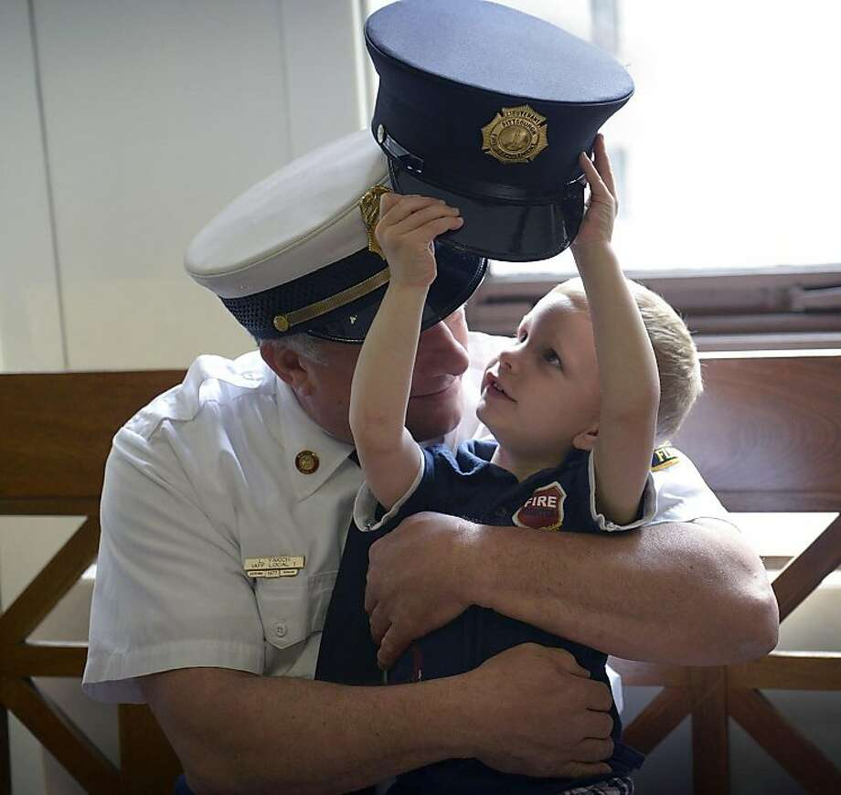 Future fireman: Two-year-old D.J.Yakich tries on a firefighter's hat with his grandfather, Battalion Chief 