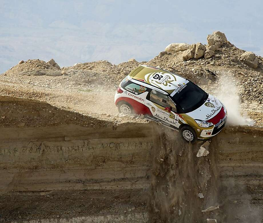'Turn right in 20 yards ... Recalculating ...' Abu Dhabi Racing driver Mohammed al-Sahlawi and co-driver Allan Harryman veer off a cliff during the first stage of the Jordan Rally in Sweimeh near the Dead 