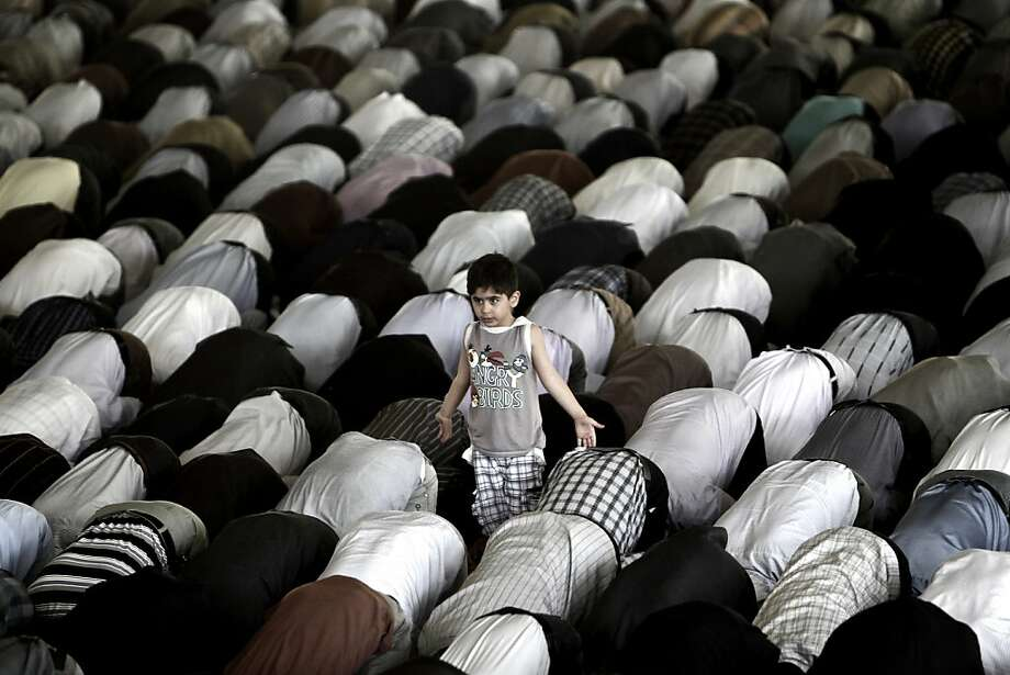 All done:An Iranian boy finishes his Friday prayers before the other Muslim worshippers at Tehran   University. Photo: Behrouz Mehri, AFP/Getty Images