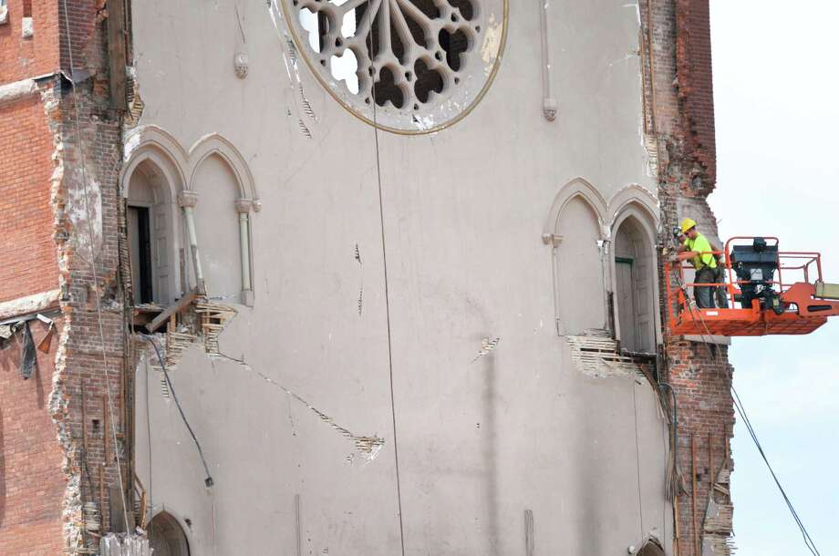 Workers attach steel cables to the bell tower at the former St. Patrick's Church in Watervliet, NY as demolition continues Friday May 10, 2013.  (John Carl D'Annibale / Times Union) Photo: John Carl D'Annibale, Albany Times Union / 00022324A