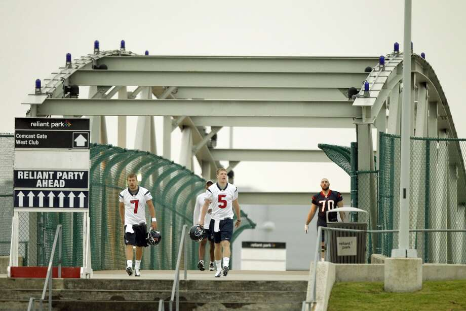 Texans quarterbacks Case Keenum (7) and Collin Klein (5) walk to practice for the opening of rookie minicamp.