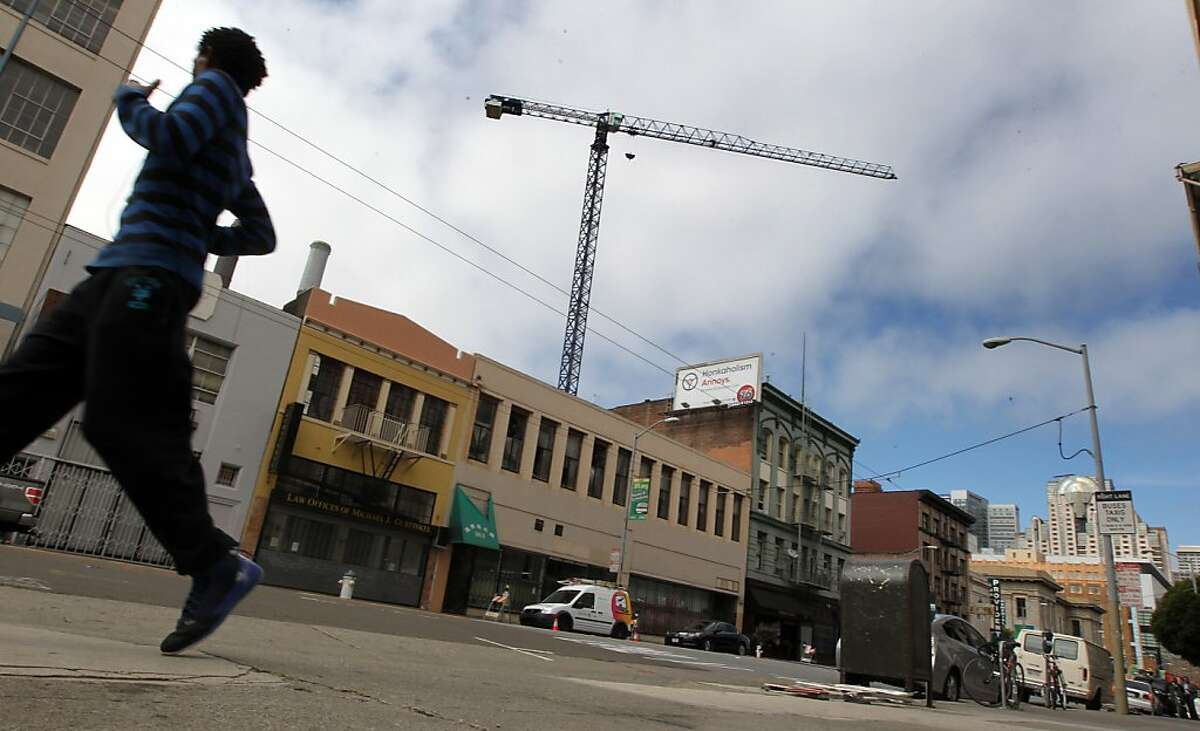 The transformation of the Mission Street between 5th and 6th is well underway with the construction of a 15-story Hampton Inn being built with the aid of a large crane. But much of the old personality remains for now, including the homeless that call these streets home. Thursday May 9, 2013. In San Francisco, California.