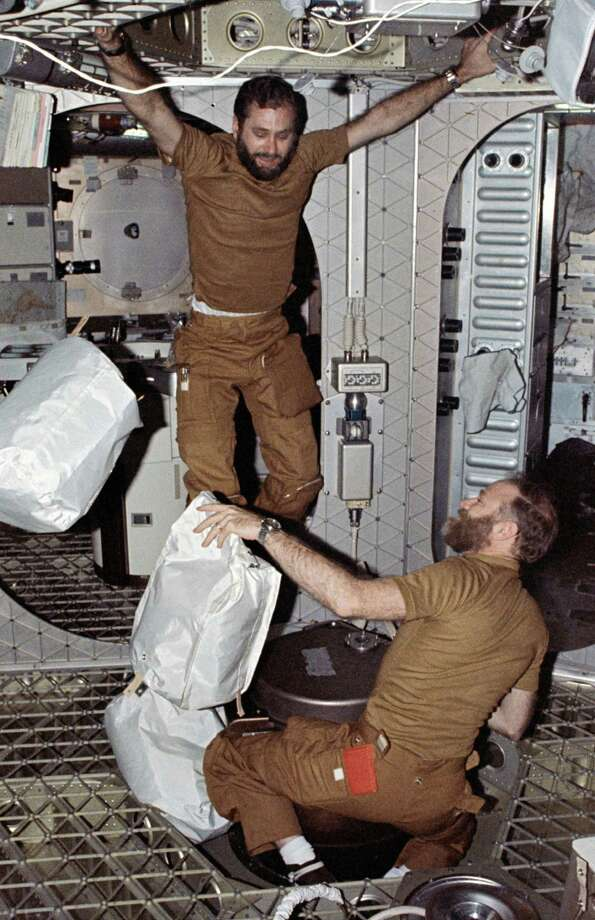 Pilot William Pogue, left, holds onto the crew quarters ceiling as he prepares to jump onto the trash airlock hatch cover to force a trash bag further down into the airlock and into a waste disposal tank. Commander Gerald Carr holds more trash bags, while another bag floats nearby. Photo: NASA
