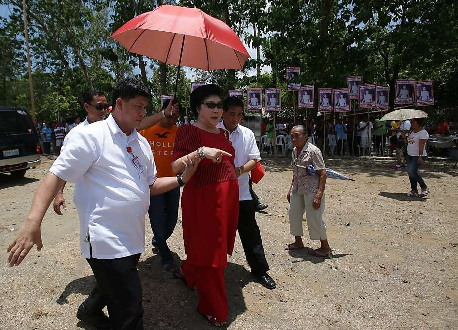 Former Philippine First Lady Imelda Marcos, center, is assisted as she walks during an electoral campaign in Ilocos Norte province, northern Philippines. Twenty-seven years after her dictator husband was ousted by a public revolt, Imelda Marcos has emerged as the Philippines' ultimate political survivor: She was back on the campaign trail this week, dazzling voters with her bouffant hairstyle, oversized jewelry and big talk in a bid to keep her seat in Congress.  Photo: Aaron Favila, Associated Press