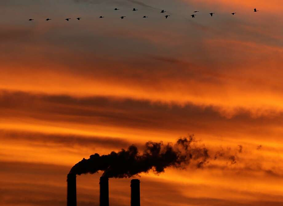 In this Sunday, Dec. 2, 2012 photo, a flock of Geese fly past the smokestacks at the Jeffrey Energy Center coal power plant as the suns sets near Emmett, Kan. Worldwide levels of the chief greenhouse gas that causes global warming have hit a milestone, reaching an amount never before encountered by humans, federal scientists said Friday, May 10, 2013. Carbon dioxide was measured at 400 parts per million at the oldest monitoring station in Hawaii which sets the global benchmark. The last time the worldwide carbon level was probably that high was about 2 million years ago, said Pieter Tans of the National Oceanic and Atmospheric Administration. (AP Photo/Charlie Riedel) Photo: Charlie Riedel, Associated Press