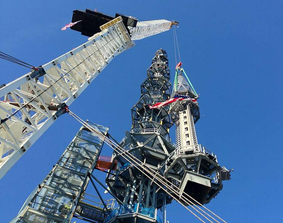 The silver spire is eased into position, bringing the structure to its symbolic height of 1,776 feet. Photo: Mark Lennihan, Associated Press