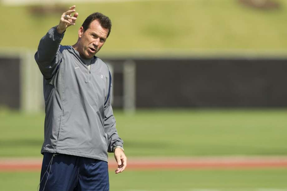 Head coach Gary Kubiak gives instructions to wide receiver DeAndre Hopkins.