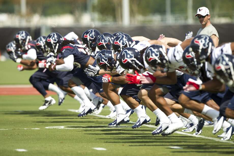 Texans players run sprints as they warm up at the beginning of practice.