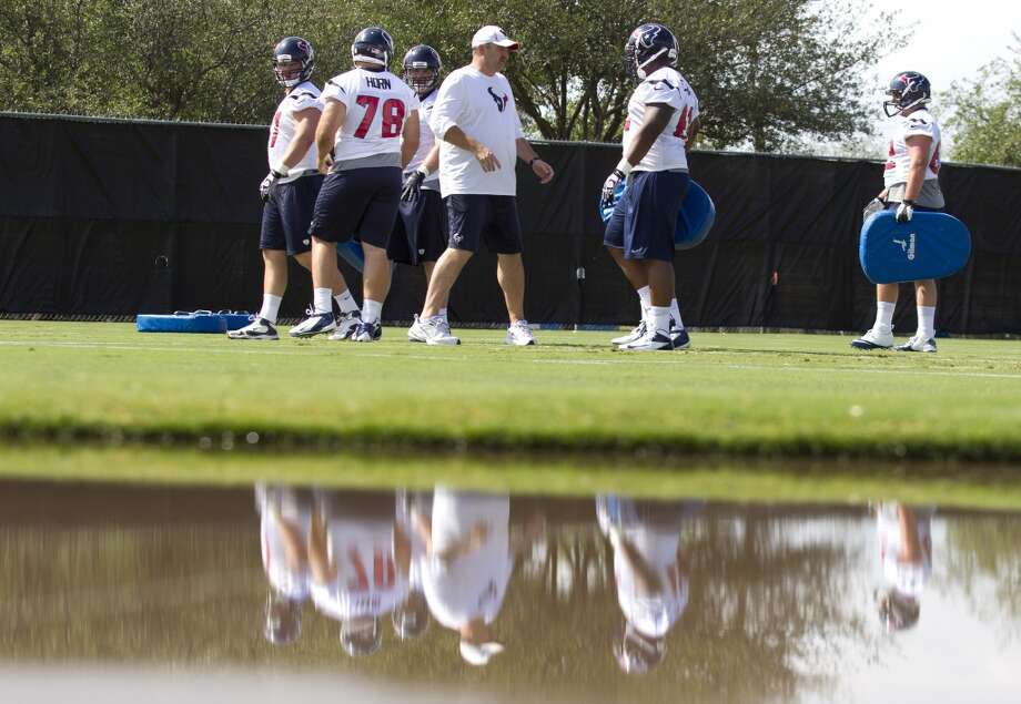 Offensive line coach John Benton, center, is reflected in a puddle of water as he runs his players through a blocking drill.