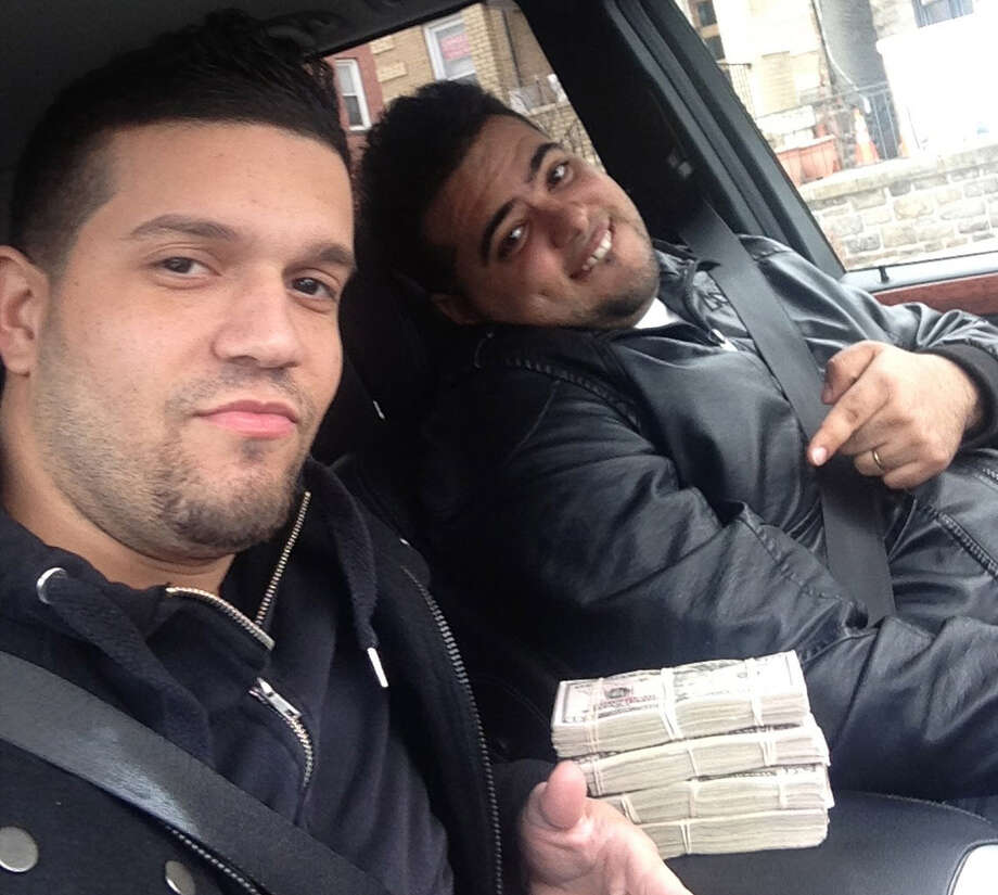 In this undated photo provided by the United States Attorney's Office for the Southern District of New York, Elvis Rafael Rodriguez, left, and Emir Yasser Yeje, pose with bundles of cash allegedly stolen using bogus magnetic swipe cards at cash machines throughout New York. Prosecutors in New York said on Thursday, May 9, 2103 said that they are members of worldwide gang of criminals who stole $45 million in hours by hacking into a database of prepaid debit cards and draining cash machines around the globe. An indictment unsealed Thursday accused U.S. cell ringleader Alberto Yusi Lajud-Pena and seven other New York suspects of withdrawing $2.8 million in cash from hacked accounts in less than a day.  (AP Photos/U.S. Attorney's Office for the Southern District of New York) Photo: Uncredited