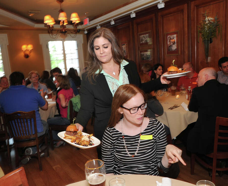 At left, Tara Bailey, manager of the Ginger Man restaurant, serves a slider, crab cake and home-made fries to Cassandra Davidson of Westport during the Dishcrawl event at the Greenwich restaurant, Wednesday, May 8, 2013. Photo: Bob Luckey / Greenwich Time