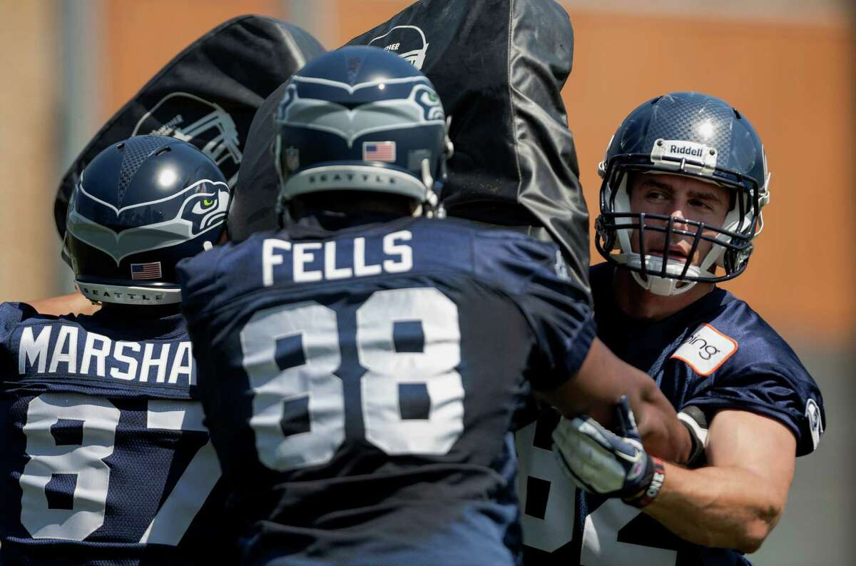 Luke Willson, right, bears the weight of two tackling players during a blocking drill on the first day of the Seahawks Rookie Minicamp Friday, May 10, 2013, at the Virginia Mason Athletic Center in Renton.