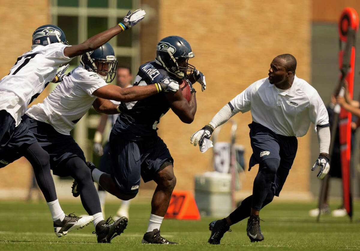 Running back Christine Michael, center, is egged on by defensive assistant Marquand Manuel, right, while pushing through a pack of defense during a scrimmage on the first day of the Seahawks Rookie Minicamp Friday, May 10, 2013, at the Virginia Mason Athletic Center in Renton.