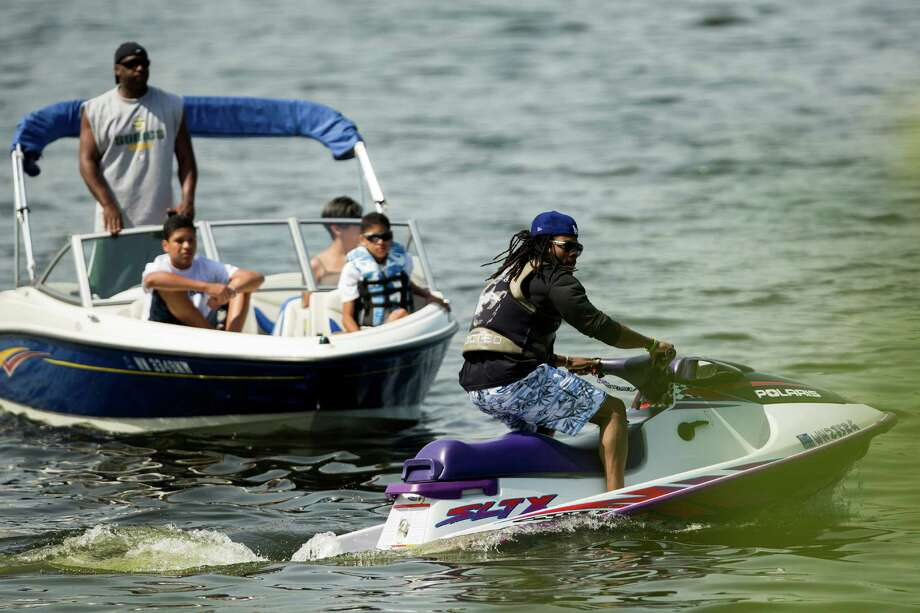 Richard Sherman, right, of the Seattle Seahawks, tries to get a view of Seahawks Rookie Minicamp from his spot on a jet ski in the waters of Lake Washington Friday, May 10, 2013, at the Virginia Mason Athletic Center in Renton. Photo: JORDAN STEAD, SEATTLEPI.COM / SEATTLEPI.COM