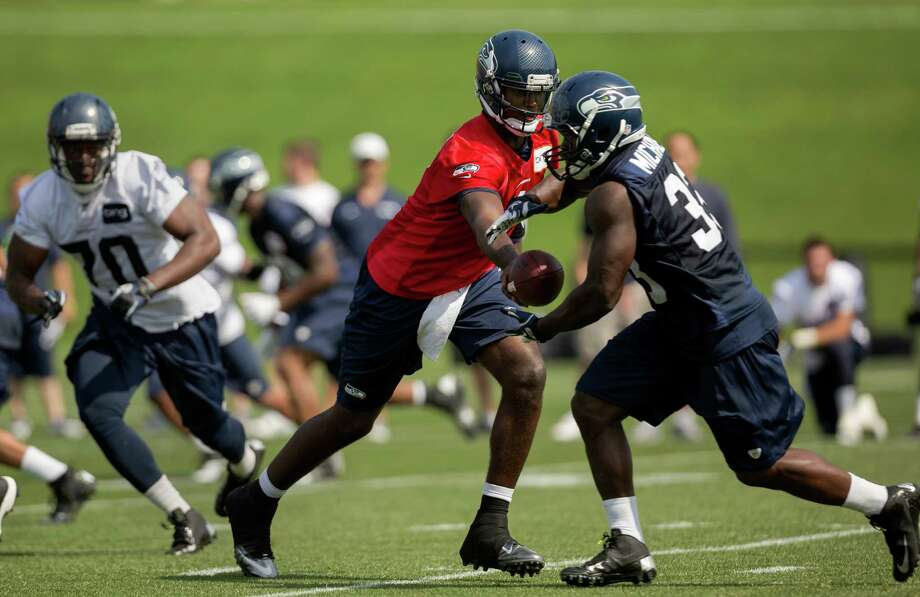 Quarterback Jerrod Johnson, center, hands off to Christine Michael, right, during a scrimmage on the first day of the Seahawks Rookie Minicamp Friday, May 10, 2013, at the Virginia Mason Athletic Center in Renton. Photo: JORDAN STEAD, SEATTLEPI.COM / SEATTLEPI.COM
