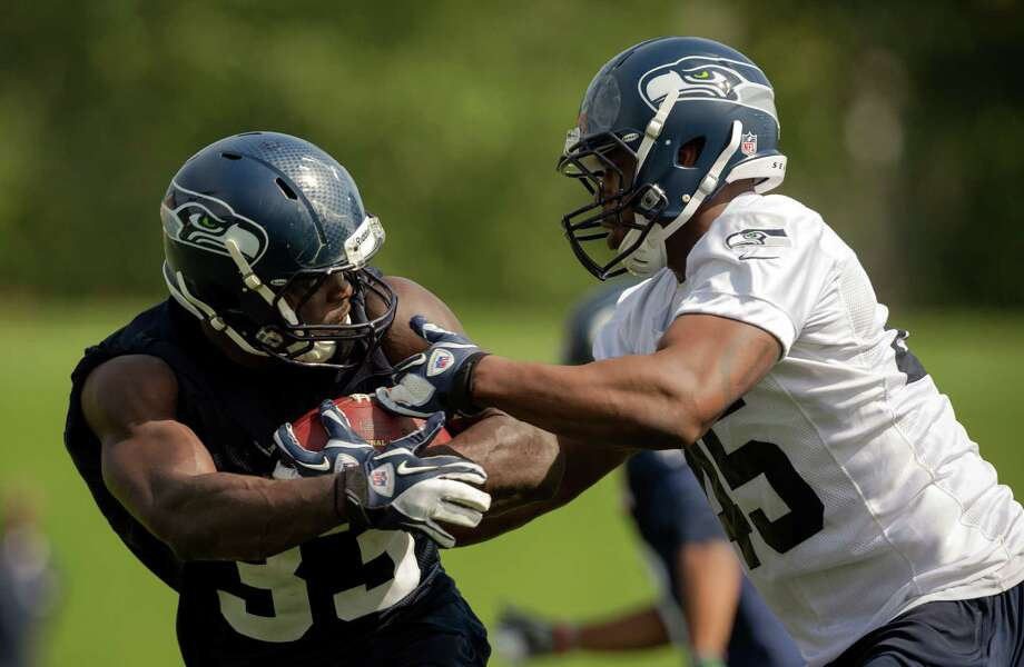 Running back Christine Michael, left, is challenged by Craig Wilkins, right, during a drill on the first day of the Seahawks Rookie Minicamp Friday, May 10, 2013, at the Virginia Mason Athletic Center in Renton. Photo: JORDAN STEAD, SEATTLEPI.COM / SEATTLEPI.COM
