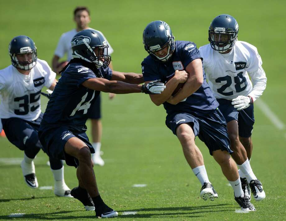 Owen Spencer, center left, attempts to wrestle the ball away during a scrimmage on the first day of the Seahawks Rookie Minicamp Friday, May 10, 2013, at the Virginia Mason Athletic Center in Renton. Photo: JORDAN STEAD, SEATTLEPI.COM / SEATTLEPI.COM