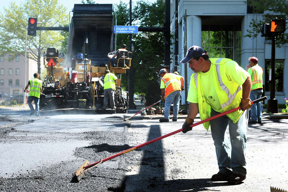 Leo Ayala, an employee of Empire Paving, works to level hot asphalt on John Street, in Bridgeport, Conn., May 10th, 2013. Traffic throughout downtown has been detoured in various directions for a couple of weeks during the major paving project. Photo: Ned Gerard / Connecticut Post