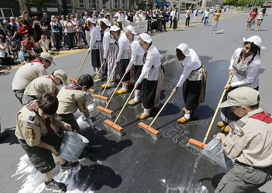 Albany High School students, dressed in traditional Dutch outfits and assisted by Boy Scouts and Cub Scouts, perform the traditional scrubbing of State Street starting the 65th Albany Tulip Festival on Friday, May 10, 2013, in Albany, N.Y. The weekend-long festival celebrates the city's Dutch heritage.  Photo: Mike Groll, Associated Press