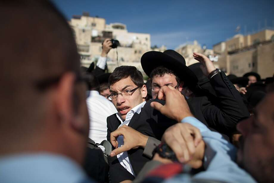 Ultra-Orthodox protestors clash with Israeli police officers during a prayer service held by the religious group 'Women Of The Wall' to mark the first day of the Jewish month of Sivan at the Western Wall on May 10, 2013 in Jerusalem, Israel. Thousands of ultra-Orthodox protestors clashed with Israeli police during the first monthly prayer service to be held by Women Of The Wall following the recent landmark ruling by Jerusalem District Court allowing women to wear prayer shawls at the Western Wall.  Photo: Uriel Sinai, Getty Images
