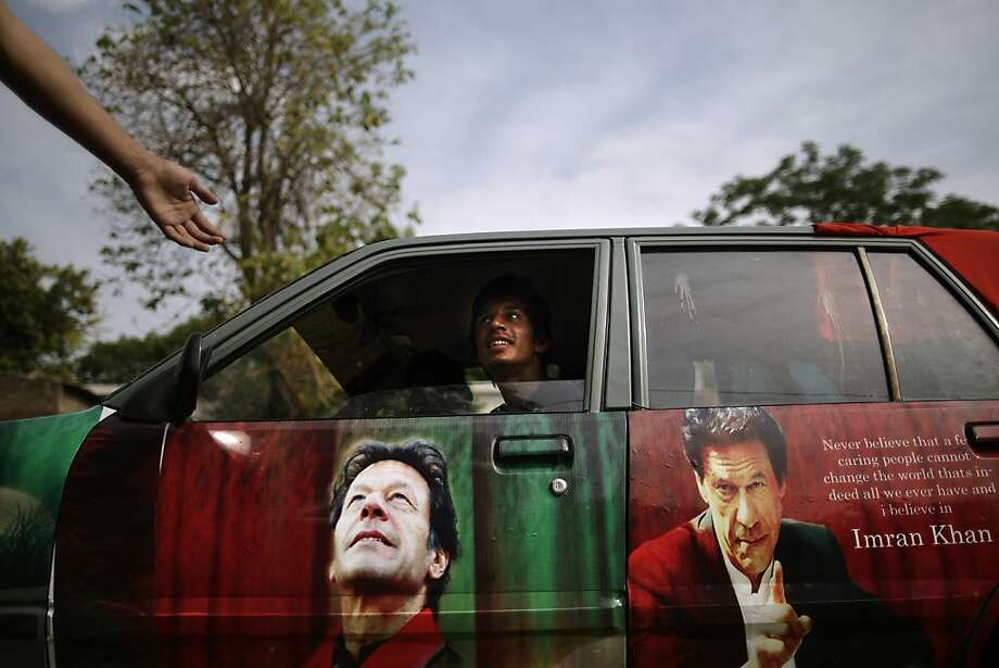 A Pakistani supporter of former cricket star-turned-politician, and leader of Pakistan Tehreek-e-Insaf party, Imran Khan, talks with another from his car decorated with pictures bearing the image of Khan, in Islamabad, Pakistan, Friday, May 10, 2013. An especially violent spate of killings, kidnappings and bombings marred the run-up to Pakistan's nationwide election, capped Thursday by the abduction of the son of a former prime minister as he was rallying supporters on the last day of campaigning before the historic vote.  Photo: Muhammed Muheisen, Associated Press