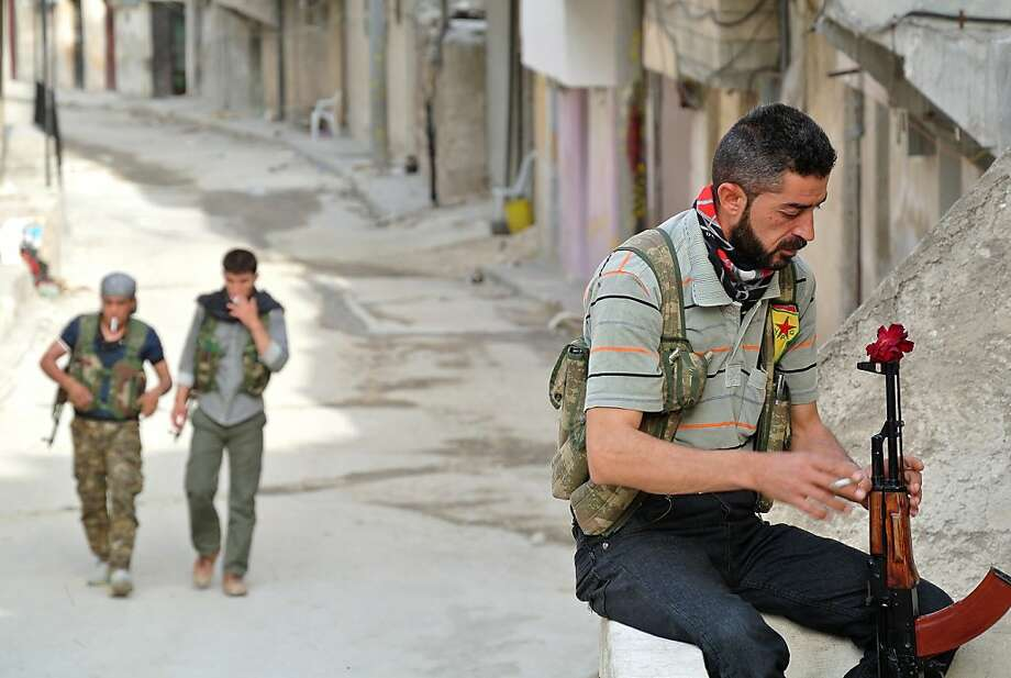 A rebel fighter of the Syrian Kurdish Popular Protection Units (YPG) has a flower in his Russian made 'AK-47' kalashnikov gun as he holds a position in the Sheikh Maqsoud neighborhood in the Syrian city of Aleppo on May 9, 2013.  Photo: -, AFP/Getty Images