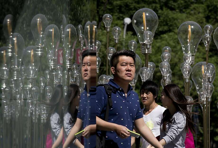 "'I have an idea!' 'So do I!' 'Me too!':Shoppers pass under the art work ""Filament Lamp"" on display at a mall in Beijing. Photo: Andy Wong, Associated Press"