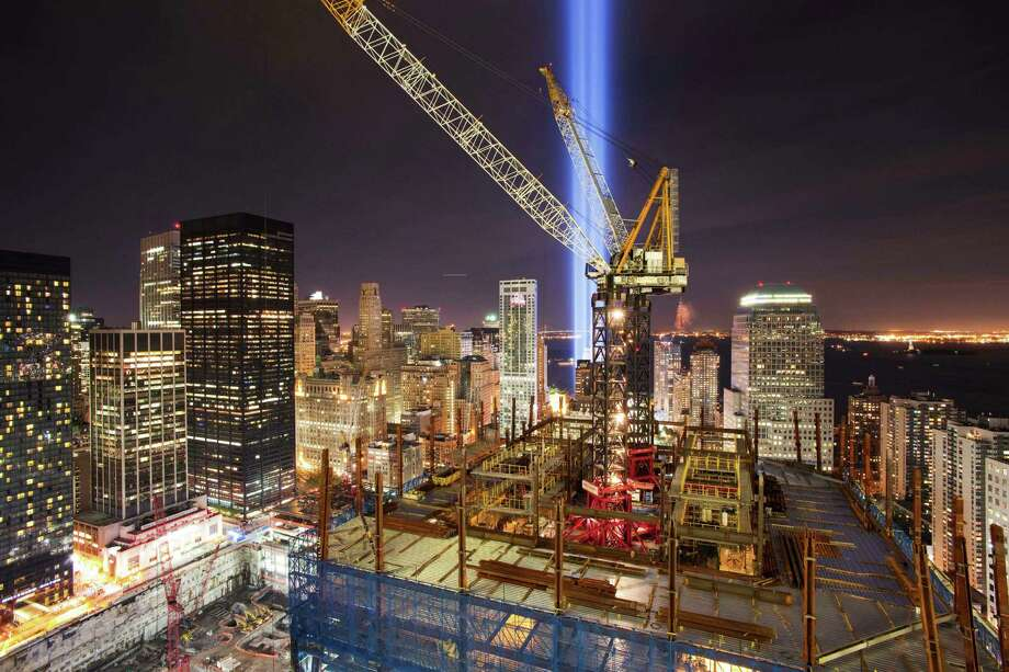 "In this Sept. 11, 2010 file photo, the ""Tribute in Light"" shines above the construction cranes on One World Trade Center, and the lower New York skyline. In an annual tradition, the two bright blue beams of light are projected from lower Manhattan, in memory of the fallen twin towers. One World Trade Center's spire was fully installed atop One World Trade Center on Friday, May 10, 2013, bringing the New York City structure to its symbolic height of 1,776 feet. Photo: Mark Lennihan, Associated Press / AP"