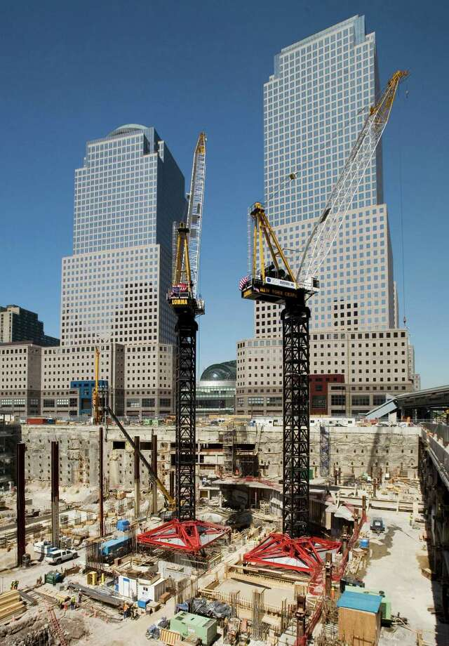 "In this May 30, 2007 file photo, construction cranes work over the ""Freedom Tower"" construction site in New York. The World Trade Center, destroyed in the attacks of Sept. 11, 2001, will be anchored by One World Trade Center, as well as three additional office towers, a memorial and a transportation hub. The World Financial Center buildings in the background are occupied by Merrill Lynch, left, and American Express. Photo: Mark Lennihan, Associated Press / AP"