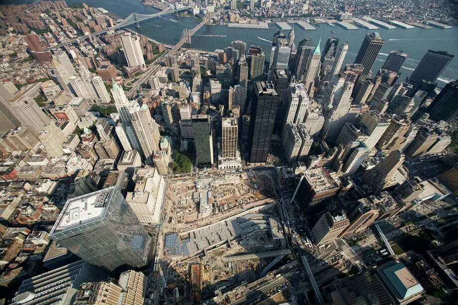 This Aug. 29, 2007 file photo shows the World Trade Center site, center, surrounded by skyscrapers in New York. Installation of the 408-foot, 758-ton spire on One World Trade Center was completed Friday, May 10, 2013. It will serve as a world-class broadcast antenna and also as a beacon to ward off aircraft. Photo: Mark Lennihan, Associated Press / AP