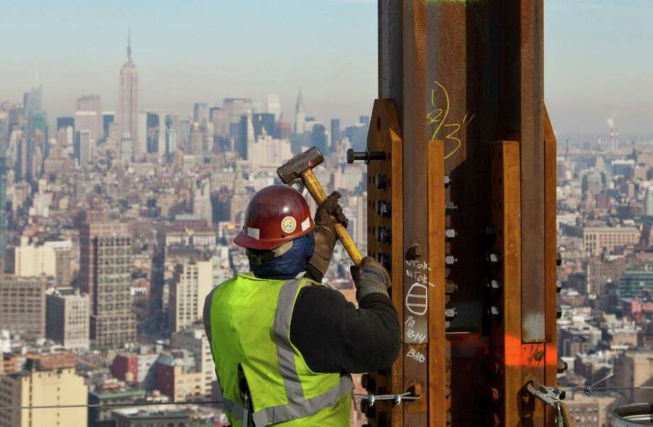 In this Dec. 16, 2010 file photo, an ironworker connects a steel plate to a column at One World Trade Center in New York. The Empire State Building is visible in the rear upper left. Photo: Mark Lennihan, Associated Press / AP