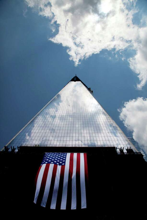 In this June 14, 2012 file photo, an American flag is draped on the side of One World Trade Center in New York. Photo: Mark Lennihan, Associated Press / AP