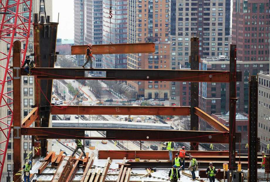 In this March 25, 2010 file photo, an ironworker walks on a beam as he guides another beam suspended from a crane at One World Trade Center construction site in New York. Photo: Mark Lennihan, Associated Press / AP
