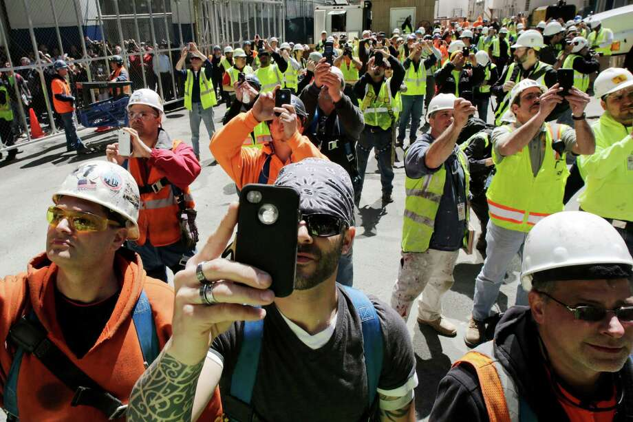 In this May 2, 2013 file photo, construction workers watch and take photos with their phones as the final piece of spire is hoisted to the roof of One World Trade Center in New York. Photo: Mark Lennihan, Associated Press / AP
