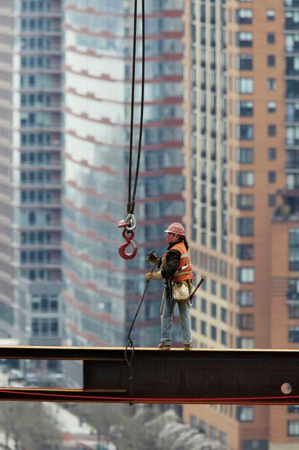 In this March 25, 2010 file photo, an ironworker unhooks a cable suspended from a crane at the One World Trade Center construction site in New York. Photo: Mark Lennihan, Associated Press / AP