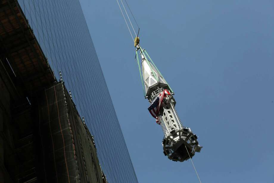 In this Thursday, May 2, 2013 photo, the final piece of spire is hoisted to the roof of One World Trade Center in New York. Photo: Mark Lennihan, Associated Press / AP
