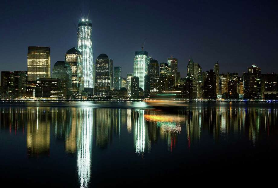 In this March 26, 2012 file photo, One World Trade Center and the Lower Manhattan skyline are reflected in the Hudson River in New York. The addition of the One World Trade Center spire on Friday, May 10, 2013, and its raising of the building's height to 1,776 feet, makes the building the tallest structure in the U.S. and third-tallest in the world, although building experts dispute whether the spire is actually an antenna - a crucial distinction in measuring the building's height. Photo: Mark Lennihan, Associated Press / AP