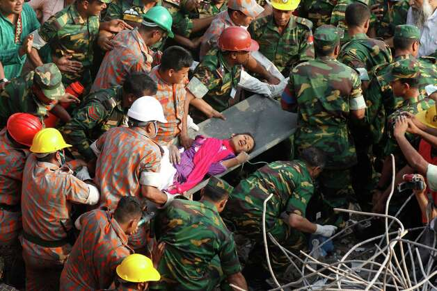 Bangladeshi rescuers retrieve garment worker Reshma from the rubble of a collapsed building in Savar on May 10, 2013, seventeen days after the eight-storey building collapsed.  The death toll from last month's collapse of a garment factory complex in Bangladesh rose past 1,000 as piles of bodies were found in the ruins of a stairwell where victims had sought shelter. Photo: STRDEL, AFP/Getty Images / AFP
