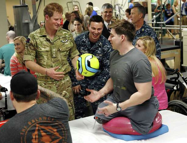 Britain's Prince Harry talks with Staff Sgt. Timothy Payne (R), who was wounded in Afghanistan, during a visit to Walter Reed National Military Medical Center in Bethesda, Maryland on May 10, 2013. Photo: KEVIN LAMARQUE, AFP/Getty Images / AFP