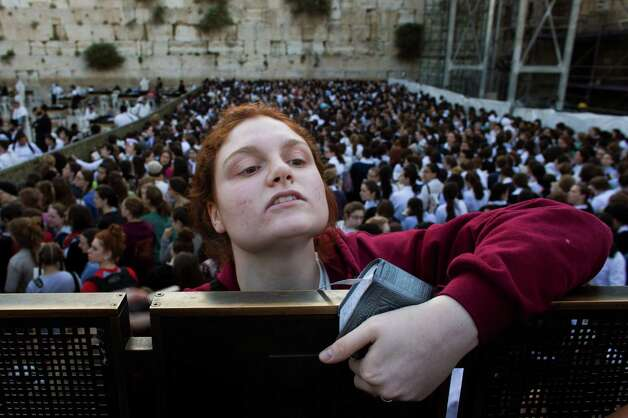 "A Jewish orthodox woman climbs a fence to get a better view of the reformist women known as the ""Women of the Wall"" organization, not pictured, at the Western Wall, the holiest site where Jews can pray in Jerusalem's old city, Friday, May 10, 2013. Israeli police with metal barriers and human chains on Friday held back hundreds of ultra-Orthodox men and women trying to prevent the ""Women of the Wall,"" a liberal Jewish women's group, from praying at the holy Western Wall, the first time police have come down on the side of the women and not the protesters. Photo: Bernat Armangue, Associated Press / AP"