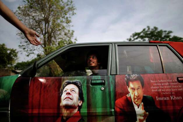 A Pakistani supporter of former cricket star-turned-politician, and leader of Pakistan Tehreek-e-Insaf party, Imran Khan, talks with another from his car decorated with pictures bearing the image of Khan, in Islamabad, Pakistan, Friday, May 10, 2013. An especially violent spate of killings, kidnappings and bombings marred the run-up to Pakistan's nationwide election, capped Thursday by the abduction of the son of a former prime minister as he was rallying supporters on the last day of campaigning before the historic vote. Photo: Muhammed Muheisen, Associated Press / AP